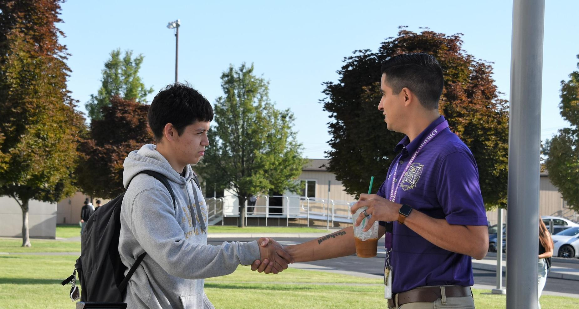 Boy shaking a counselor's hand.