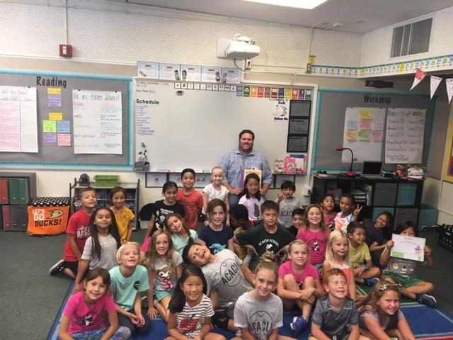 A second grade class smiling with a guest reader