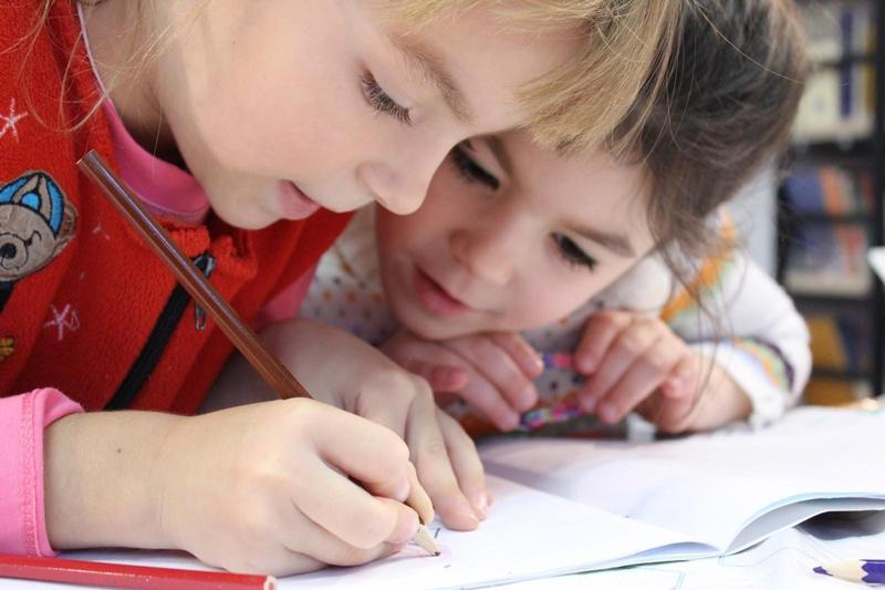 Two students leaning together. One writing with a pencil, the other is watching.