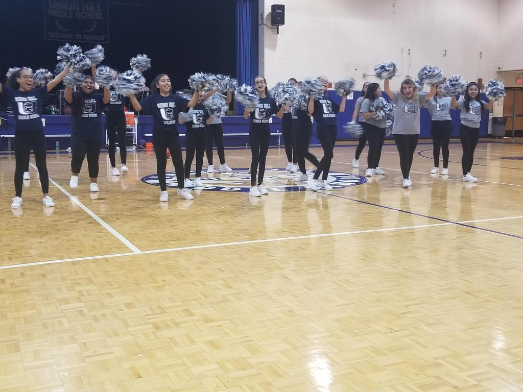 cheerleaders dancing with pom poms