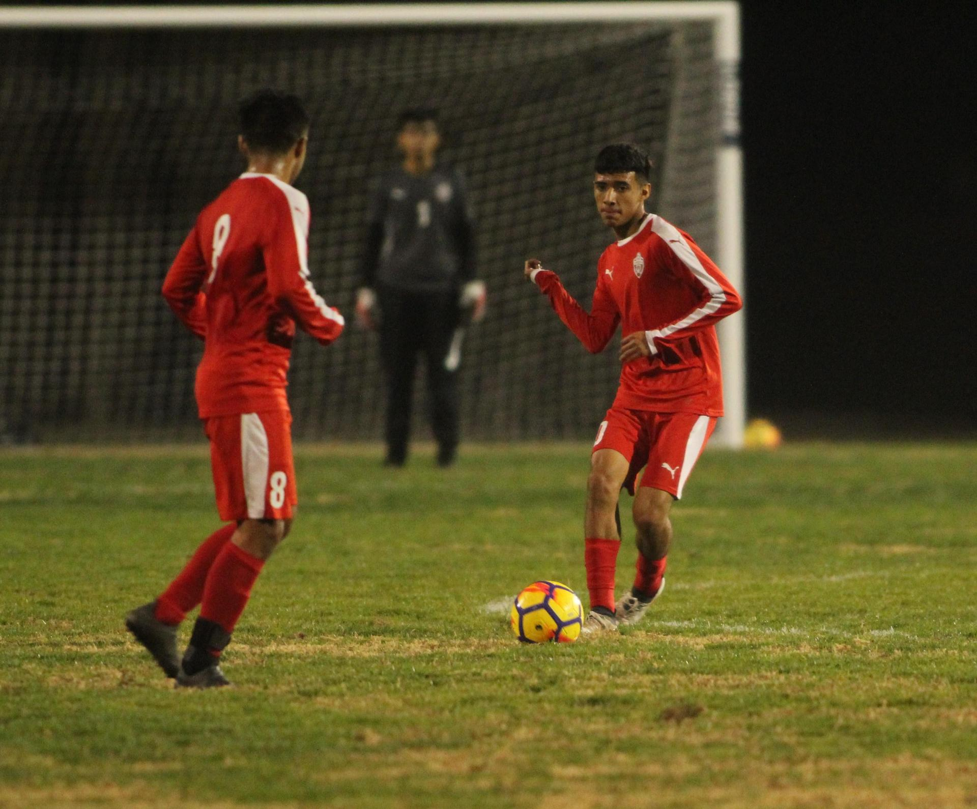 Favian Casillas and Jacob Corchado running with the ball