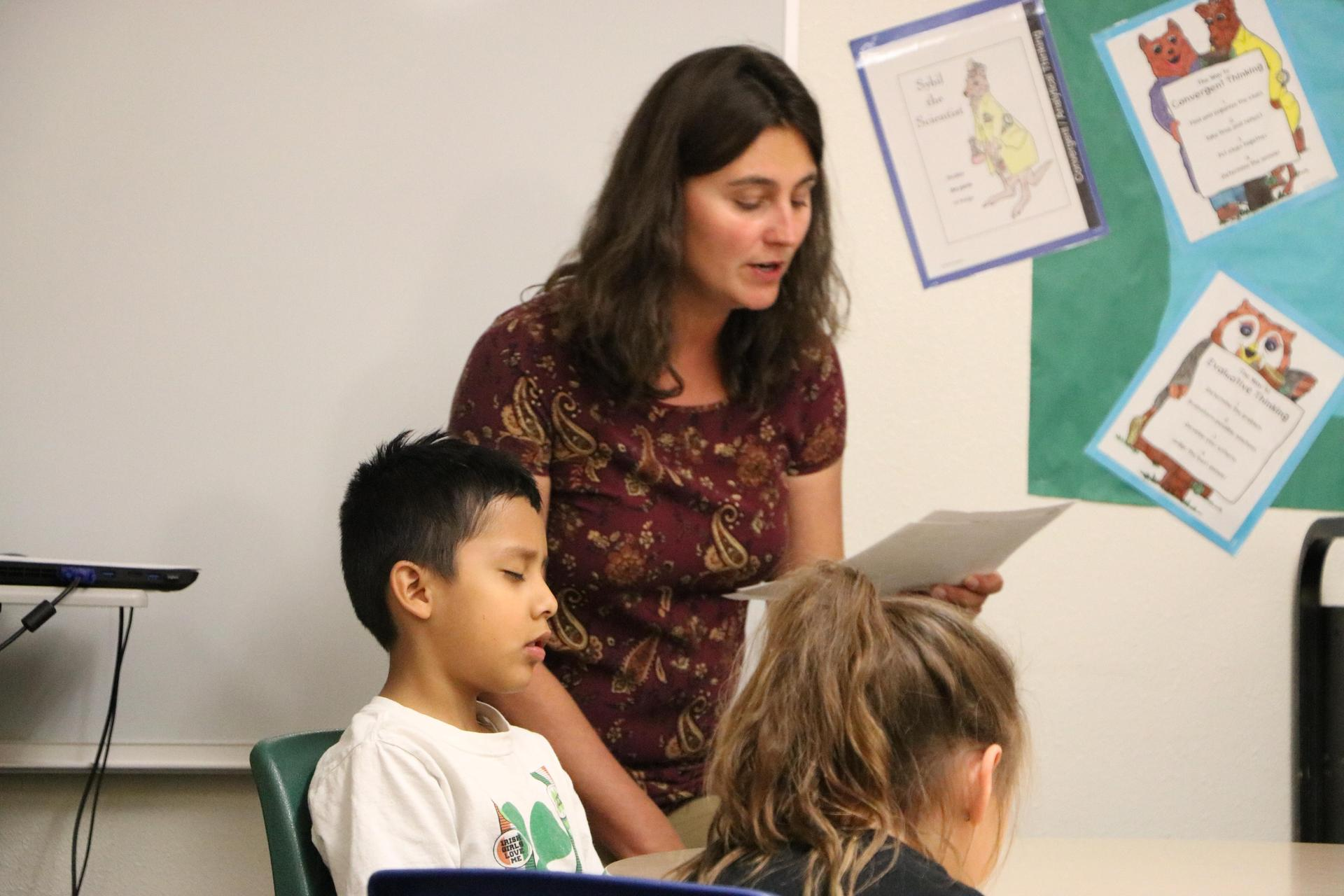 A GT Facilitator reads to a small group of students.