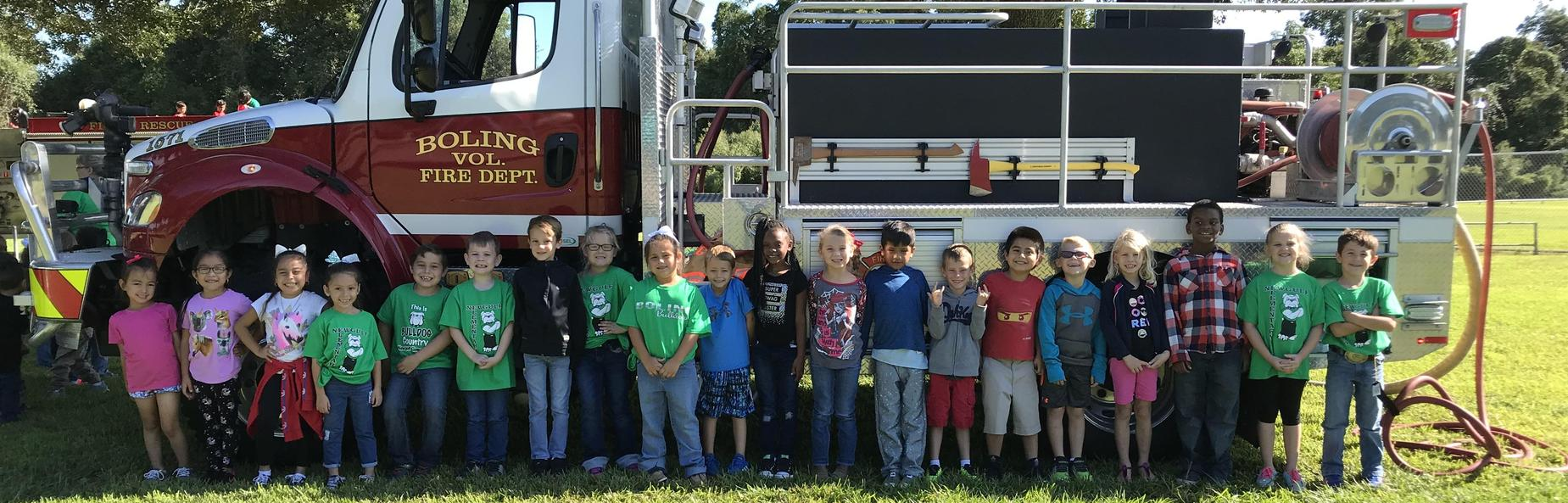 school children lined up in front of a fire truck