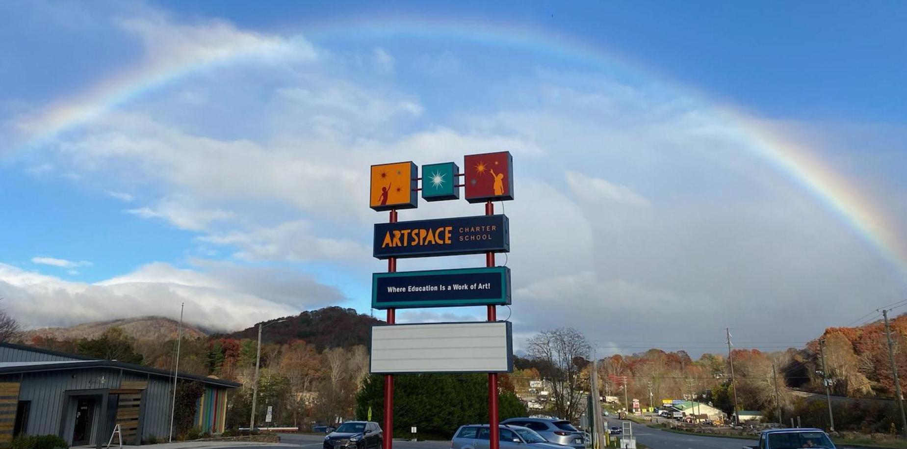 A rainbow over the school sign
