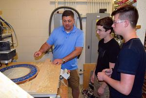 A technology education talks with students about how to use a drill press.