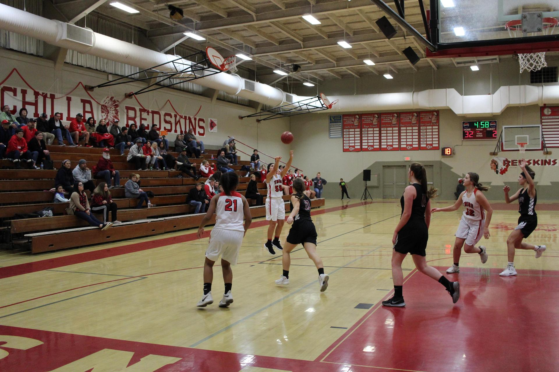 Varsity girls playing basketball against Fresno Christian