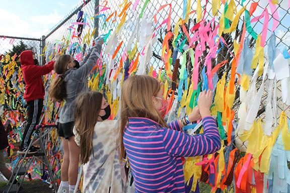 Seventh graders add more ribbons to their art installation.