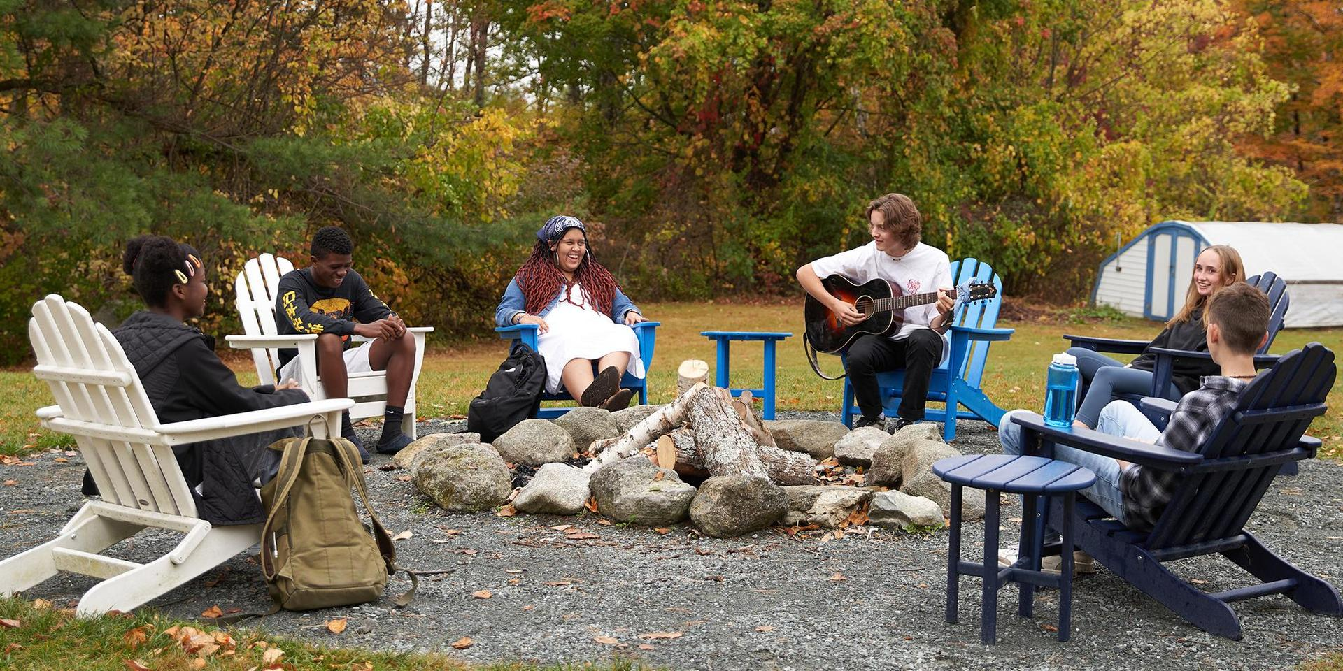 A group of students sitting around a fire pit.
