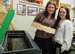 TKHS woods students Samantha Stayton and Barbar Gillhespy show the wood as it comes off the laser cutter.