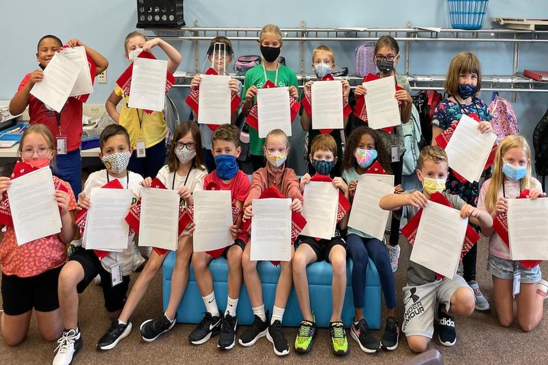 class holding report and red bandana