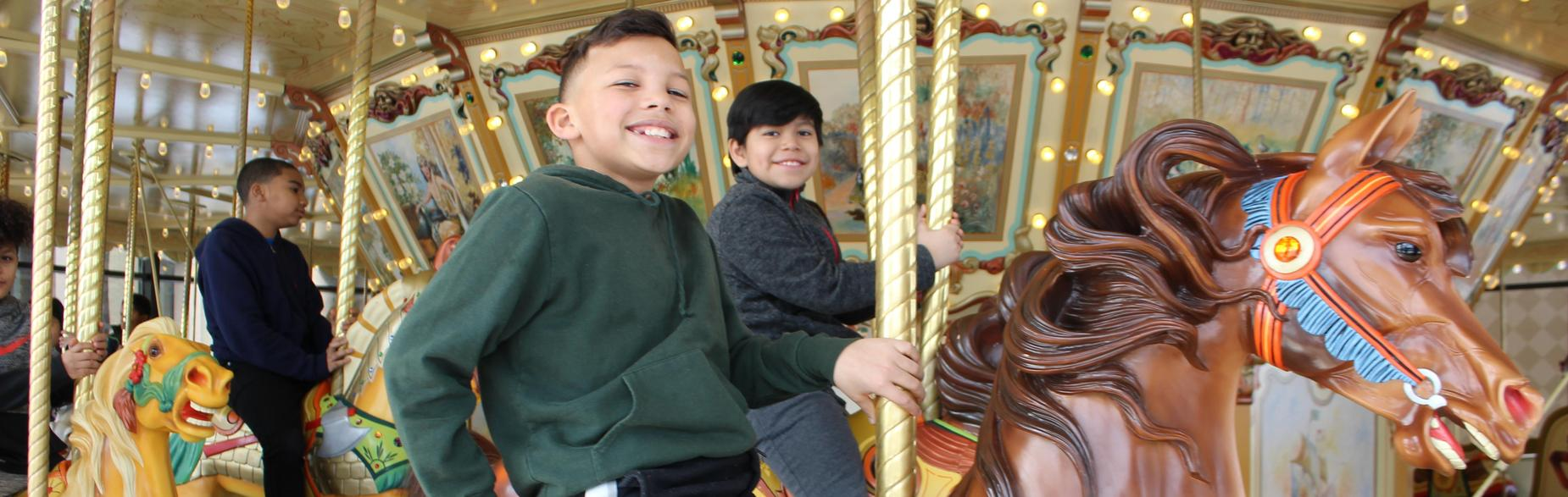 Student riding carousel