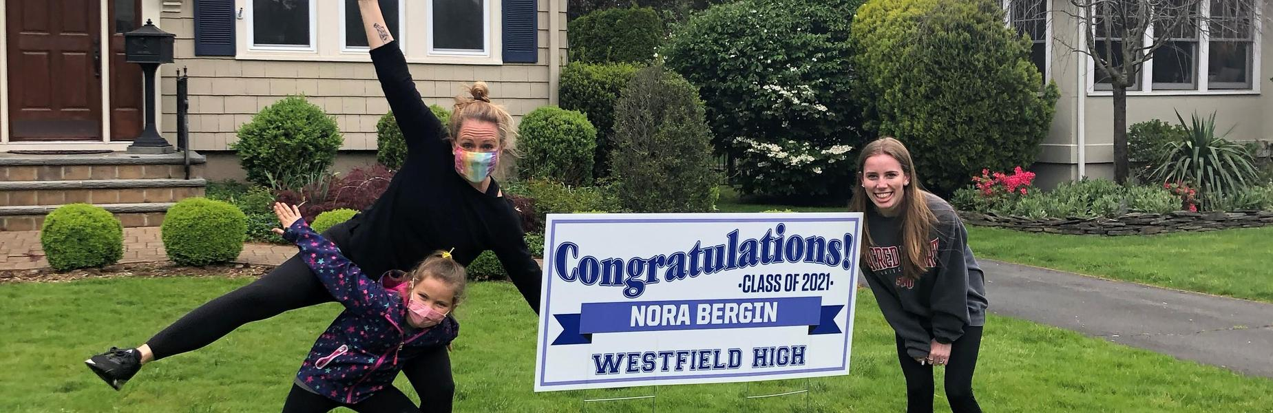 Photo of WHS 12th grader posing with lawn sign and teacher with child