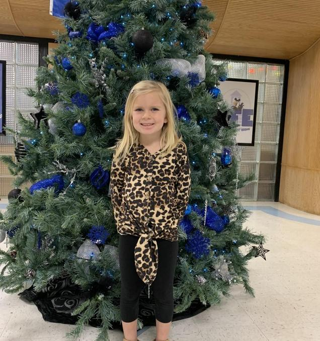 SFE student in front of Christmas Tree