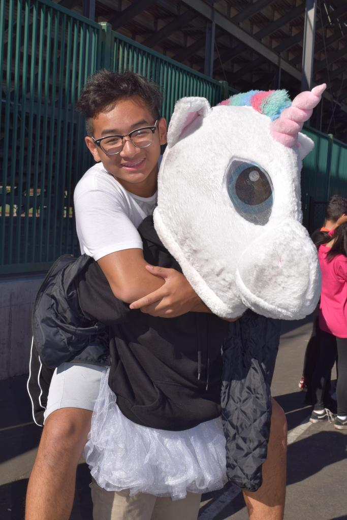 A student riding on the back of another student wearing a unicorn costume.