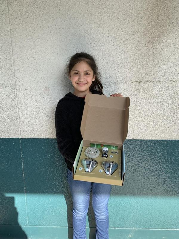 photo of a student sharing the contents of the Living Wise program box that is funded through So Cal Gas Company