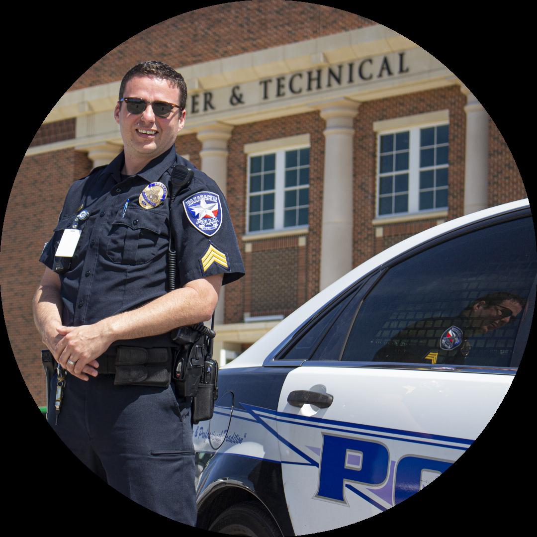 uniformed officer standing beside patrol car