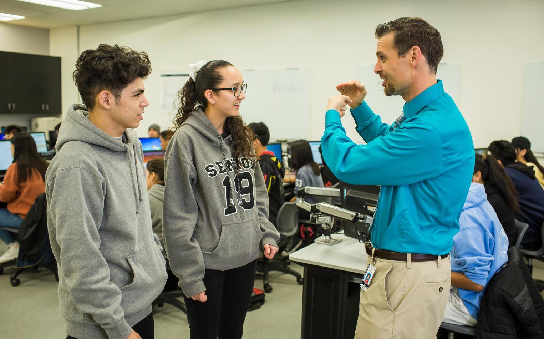 A teacher explains a computer technique to two students..