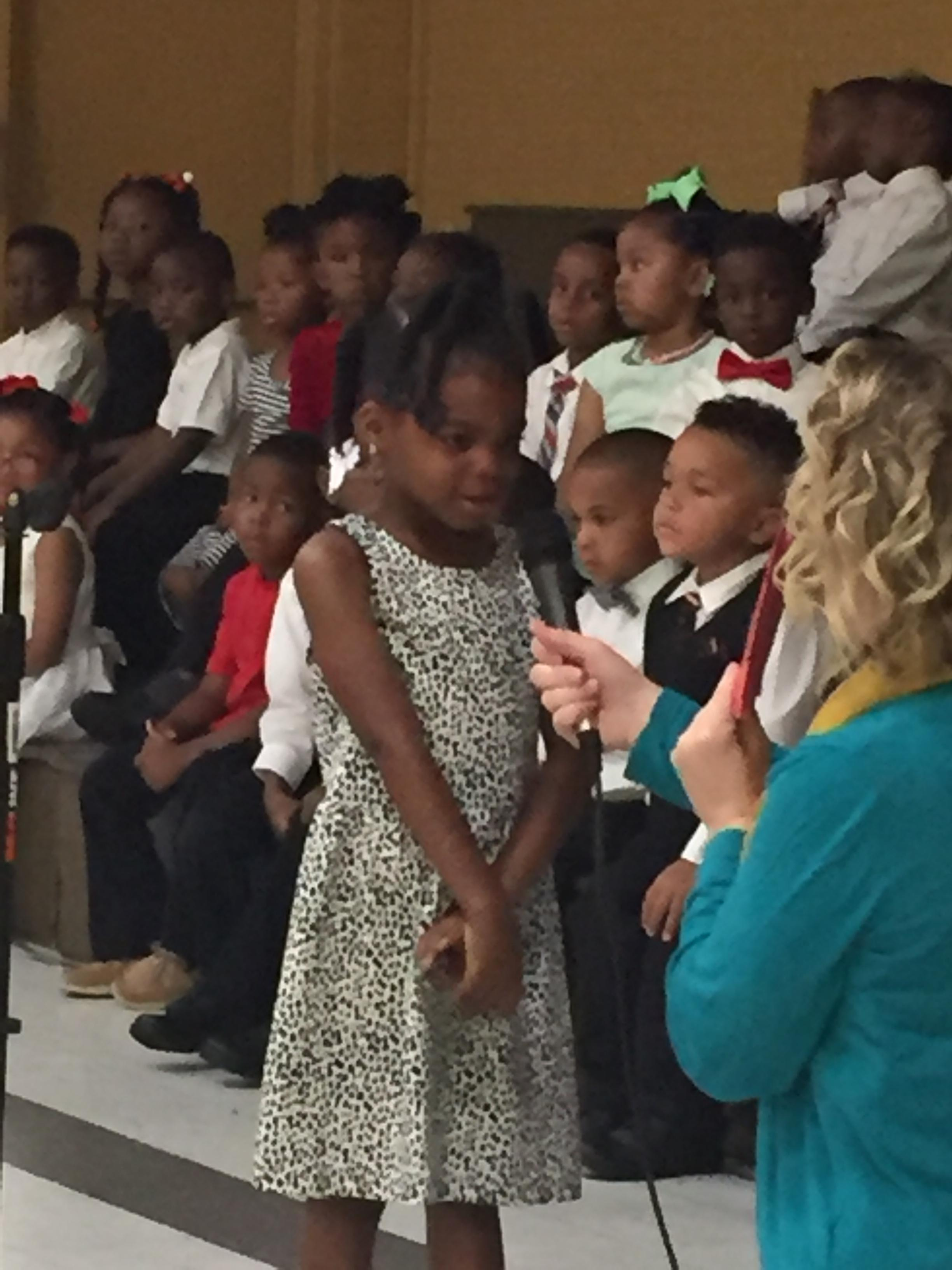 Photo of pre-kindergarten and kindergarten students at end of year awards program; a teacher is holding a microphone to the mouth of a student who is reciting
