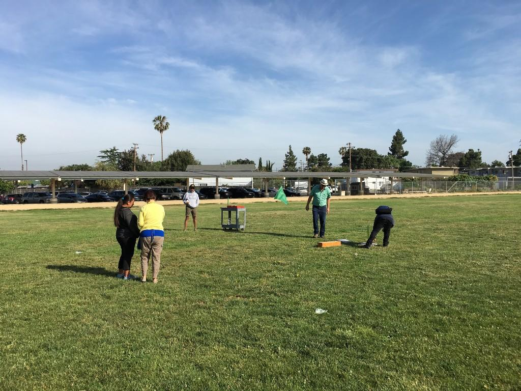 three teachers and two students in a large green field setting up rockets to launch