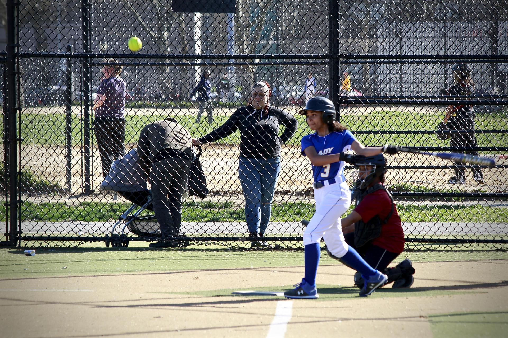 girl hitting a softball