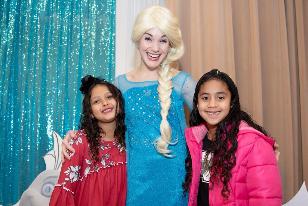 """Elsa from """"Frozen"""" with her arms around two girls"""