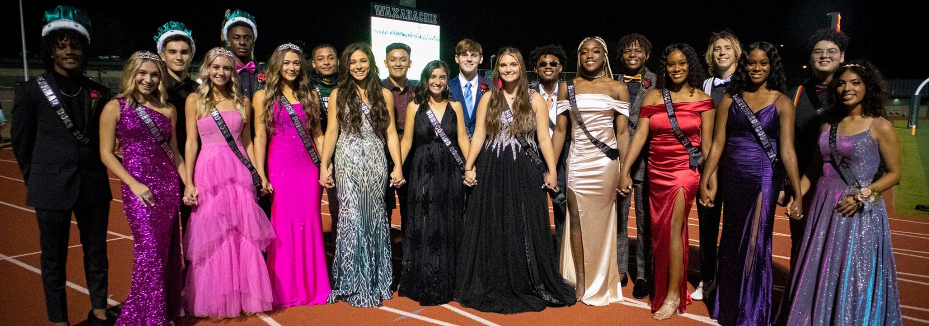 group of teens in formal wear on sidelines of football field