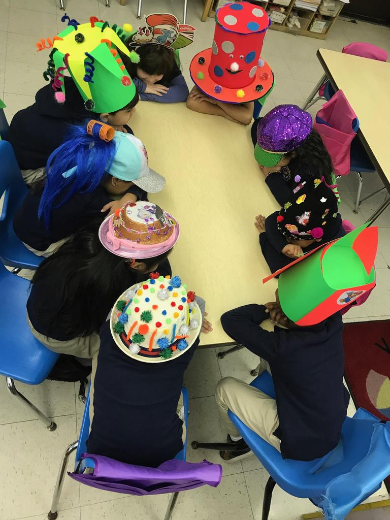 kids sitting at table with their crazy hats