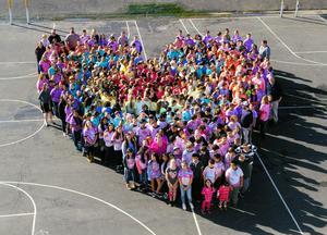 Aerial drone shot of 100s of kids in multicolored t-shirts forming a large heart on outdoor blacktop athletic courts.  Fotografía desde un dron aéreo de cientos de niños en camisetas multicolores formando un corazón en las canchas de deportes.