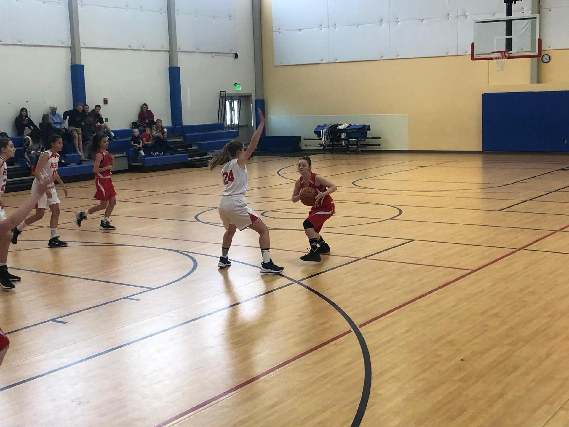 Girls basketball player playing defense