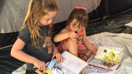 Two Gisler student's reading a book