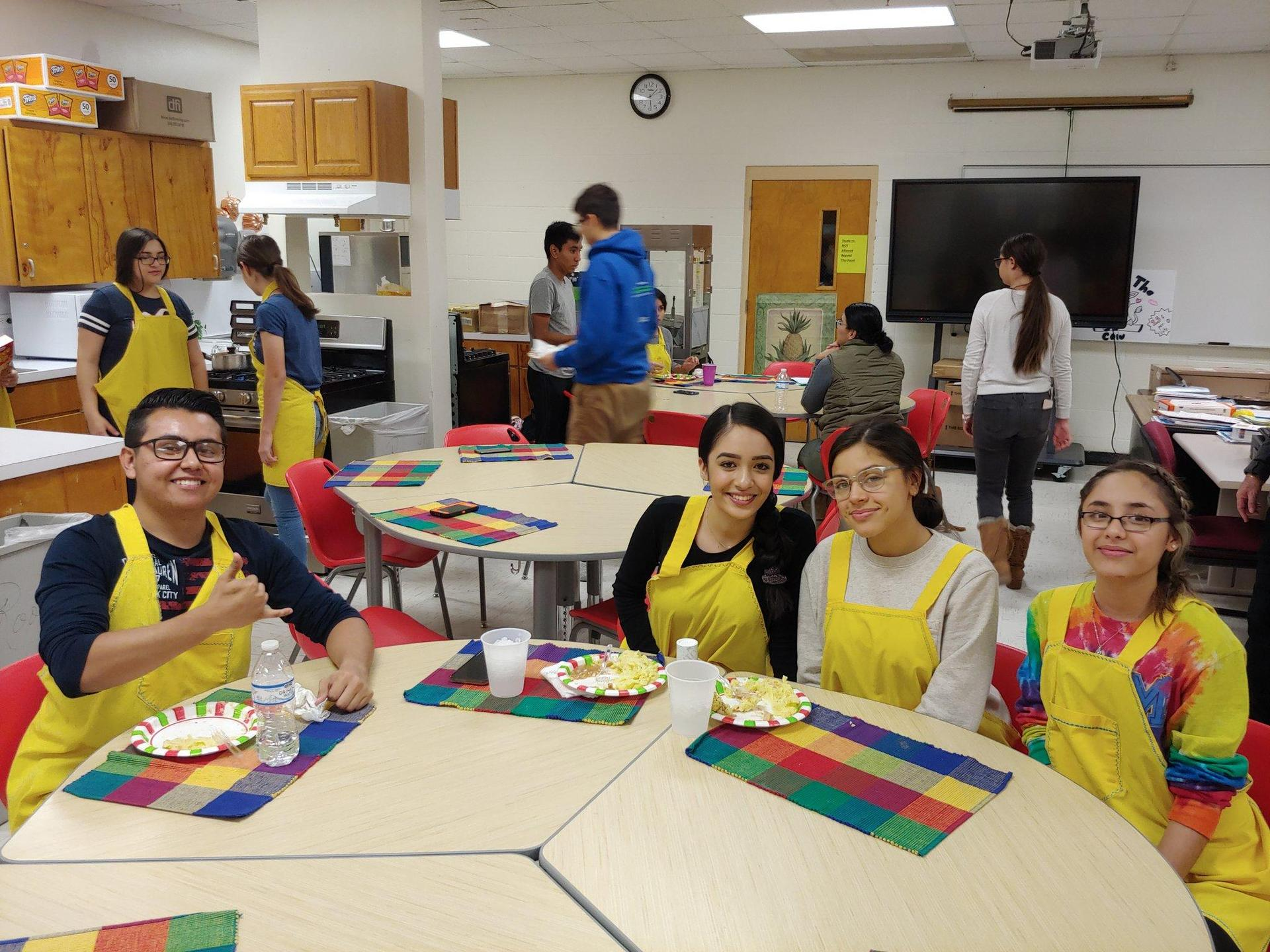 students in cooking aprons sitting in round table