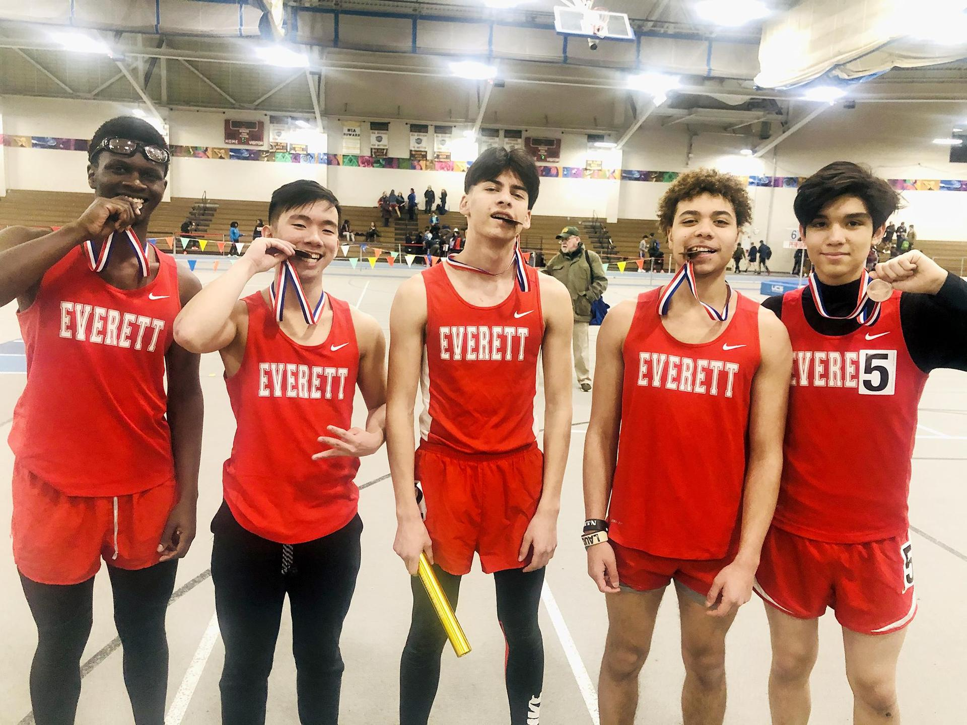 Posed photo, five male track athletes after the GBL championships