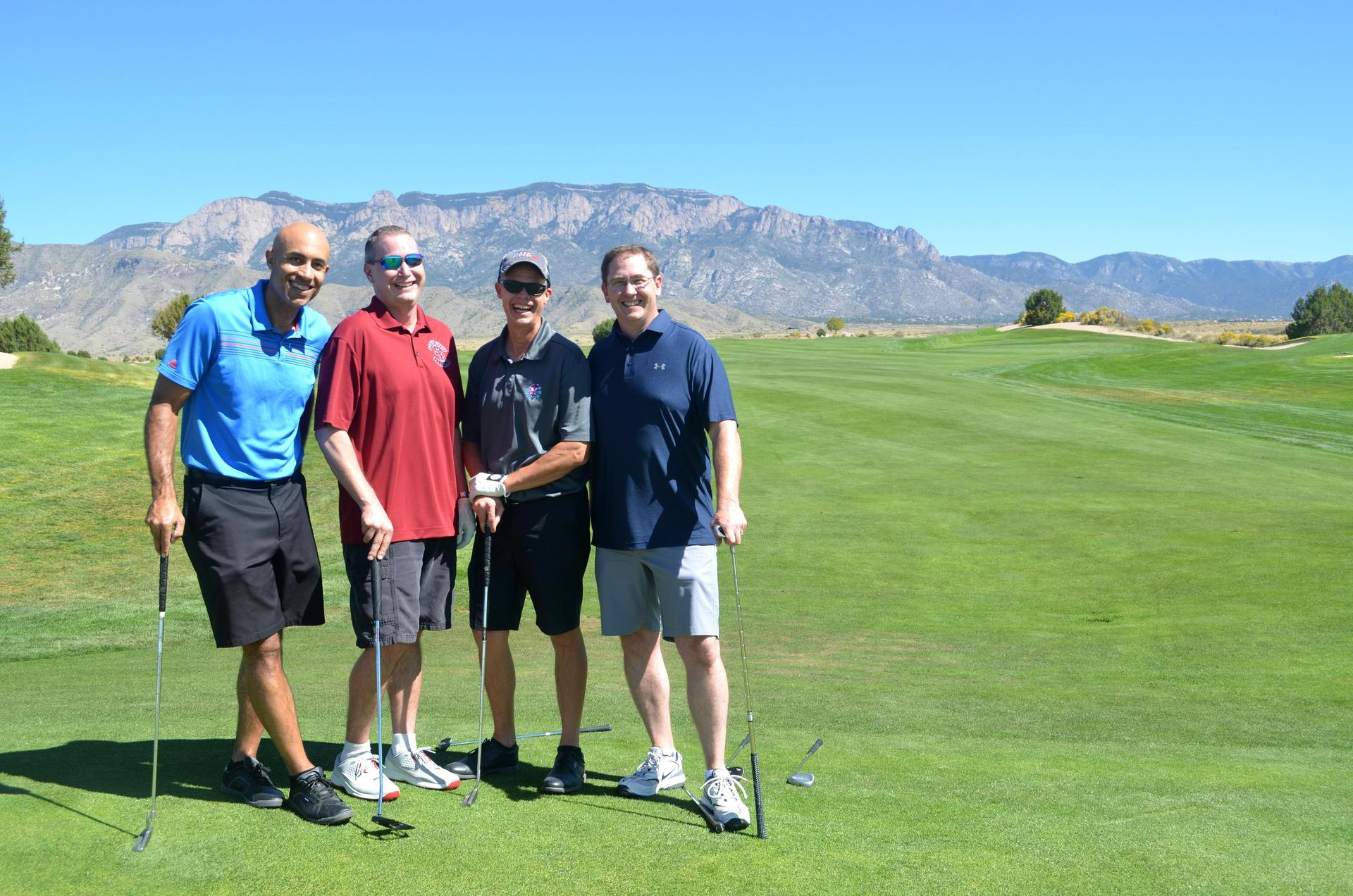Golfers smile in front of the Sandia Mountains