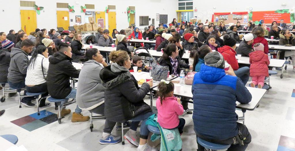 Cafeteria tables, filled with parents and families