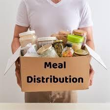 Person holding food in a box labeled meal distribution