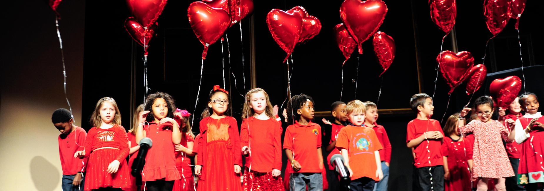 Children dressed in red with heart-shaped balloons