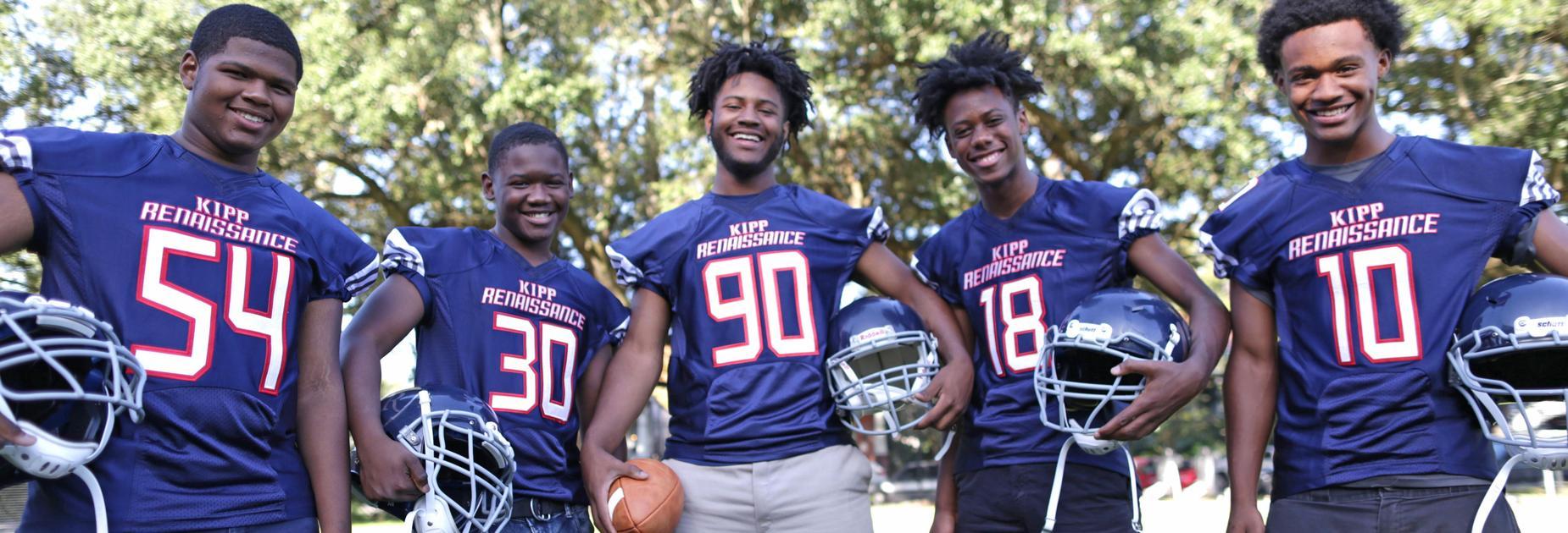 5 KRHS football team members posing in their jerseys and holding a helmet