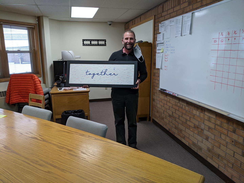 Mr. Stevenson principal holding together framed art