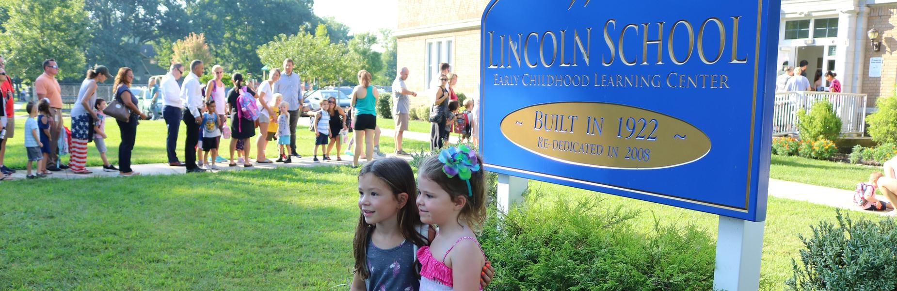 Two kindergartners stand in front Lincoln School sign on first day of school.