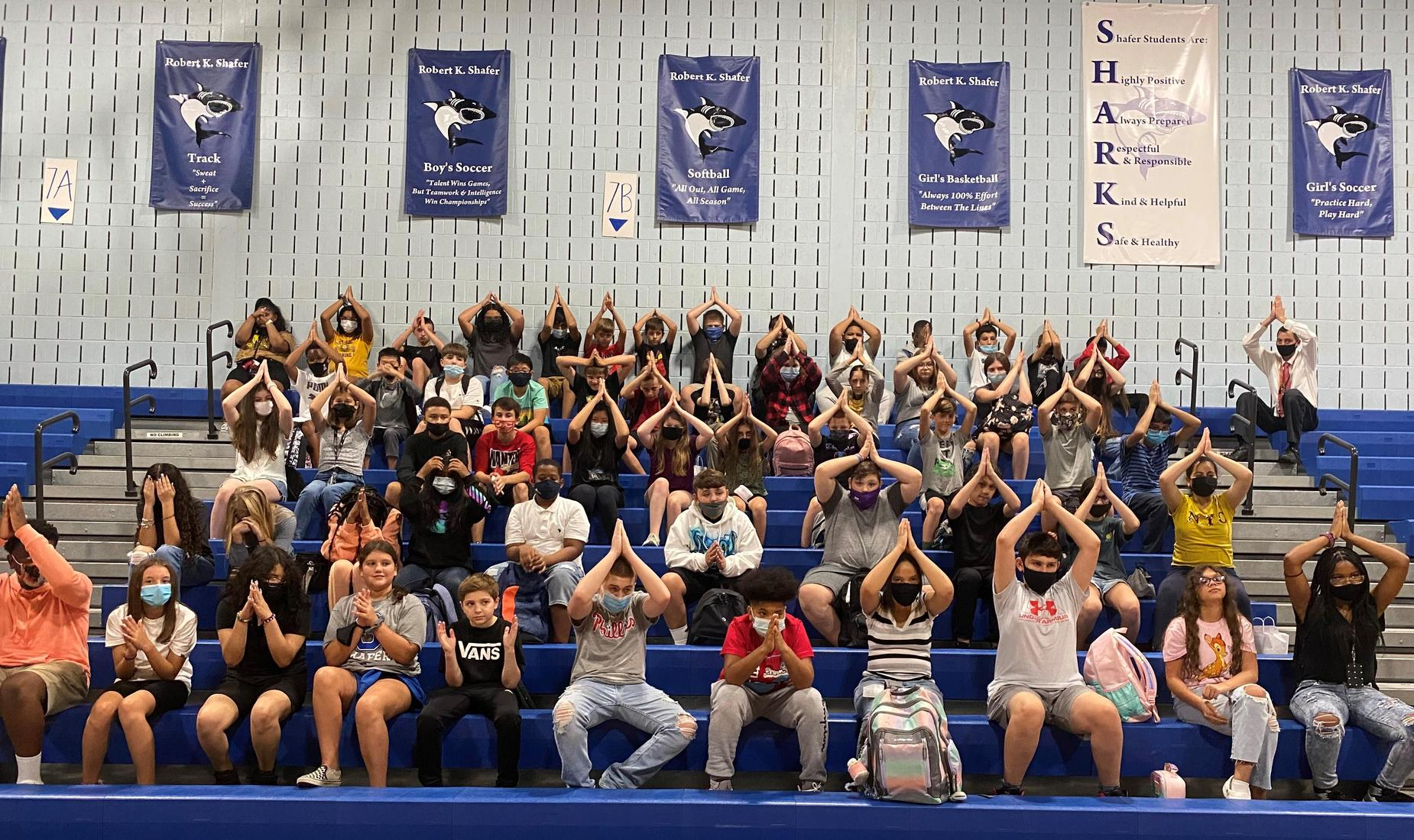 Shafer Middle Students holding their hands above their heads as though they were fins for their mascot - shark