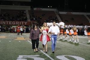 Homecoming candidate being escorted