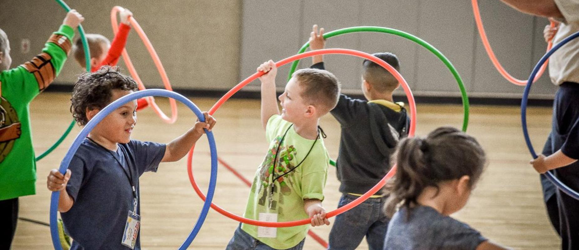 Students playing with Hula-hoops in the gym