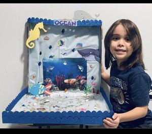 Boy smiling next to his ocean project