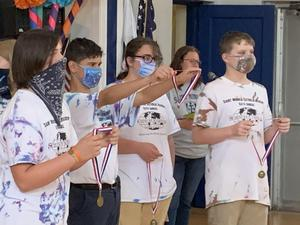 8th Grade students presenting Science Olympiad award medals