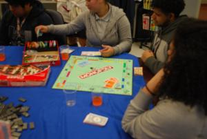 group of kids playing Monopoly