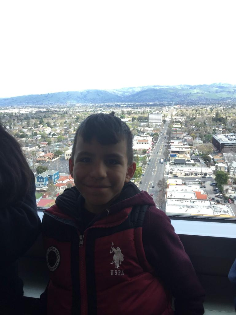 child stands in front of window with panoramic views of San Jose