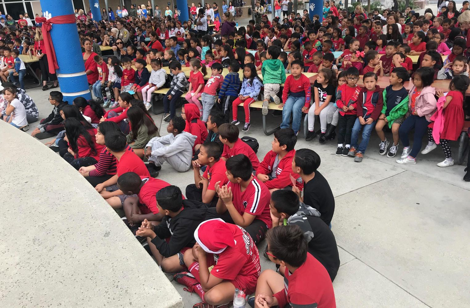 Children dressed in red sitting on lunch tables fro assembly