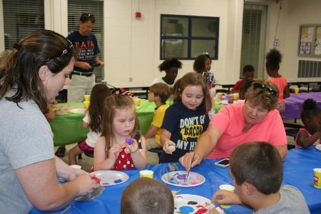 Students and parents painting rocks for Tifton Rocks.