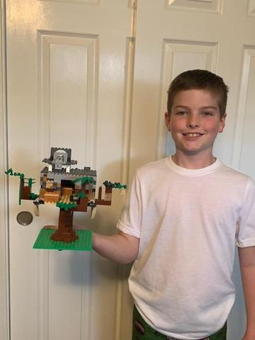 picture of student holding tree house made out of lego