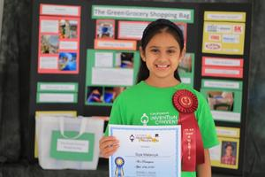 A student with her invention convention award.